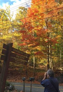 Photograph of Richard Abbott taking a picture of the Cranberry Lake Preserve sign in the autumn